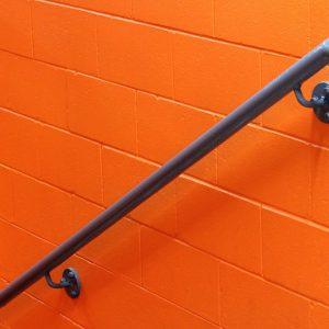 Hand railing in an orange stairwell